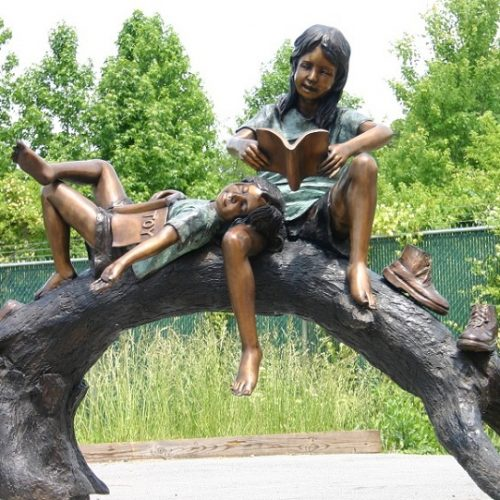 Boy and Girl Reading On A Tree Branch