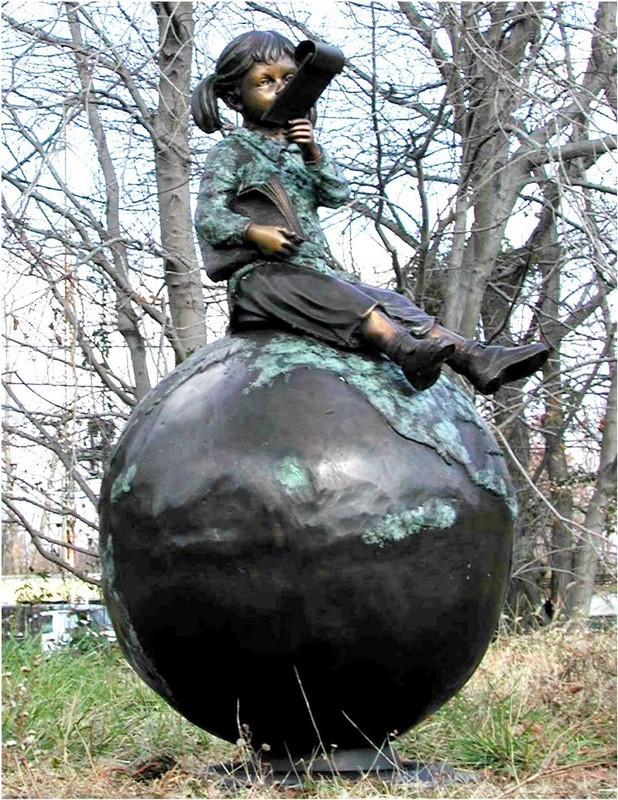 Girl sitting on a globe reading, graduation school