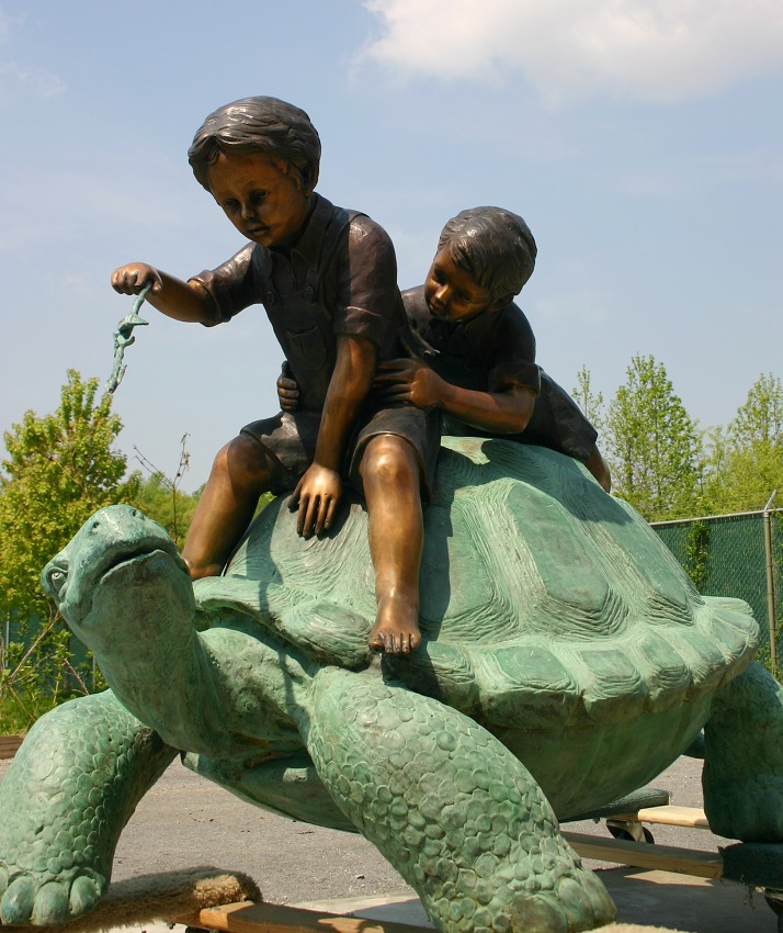 Two Boys Riding A Turtle